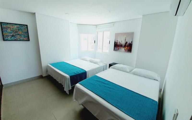 habitacion con dos camas dobles, blackout, aire acondicionado, paredes blancas y dos cuadros decorativos