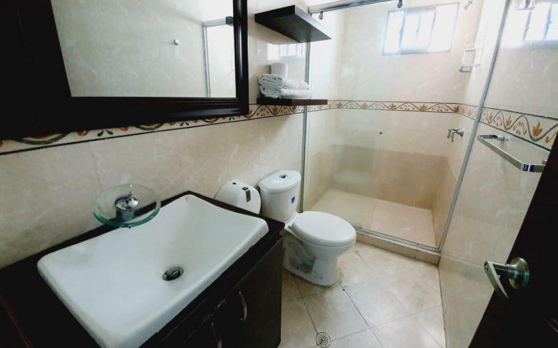 baño con baldosa color beige jaspeado, lavamanos y sanitario en ceramica color blanco, muebles en madera color wengue