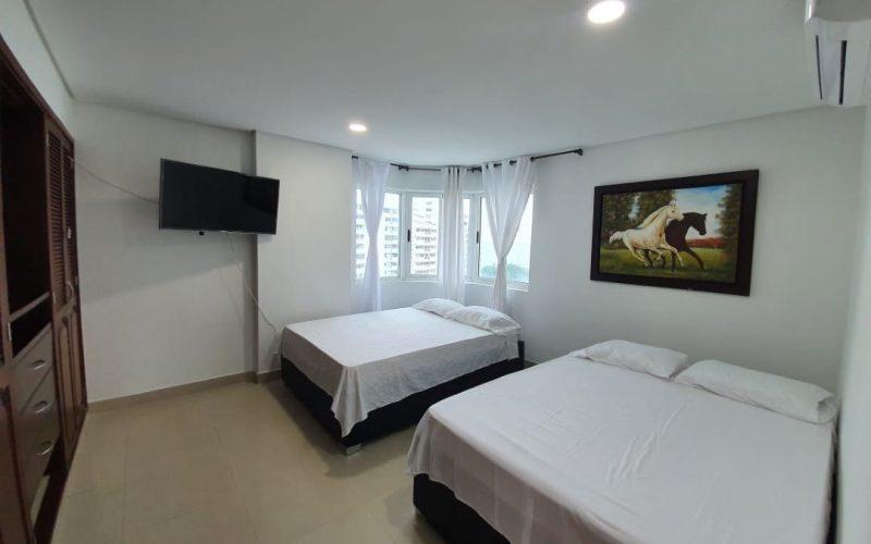 habitacion con dos camas dobles, piso en ceramica color claro, cuadro de caballos, paredes blancas, closet y aire