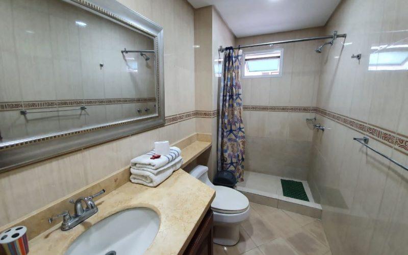 baño enchapado con ceramica cafe jaspeada, sanitario blanco y division de la ducha con cortina de colores