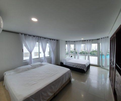 habitacion con dos camas una queen y otra sencilla, paredes blancas, closet en madera y aire acondicionado