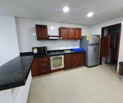 cocina con meson en granito color oscuro, gabinetes en madera color, horno y nevera color gris